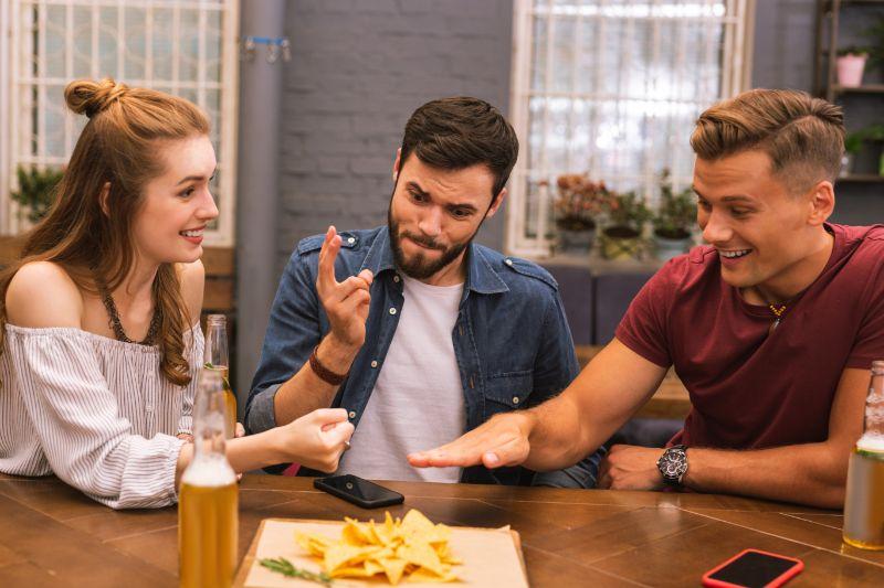Lustige-junge-Freunde-lacheln-und-spielen-Stein-schere-papier-in-der-Bar