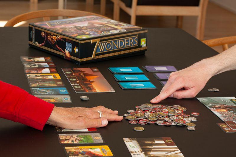 Nahaufnahme-der-Hande-von-Leuten-die-das-Brettspiel-7-Wunder-ausuben-1