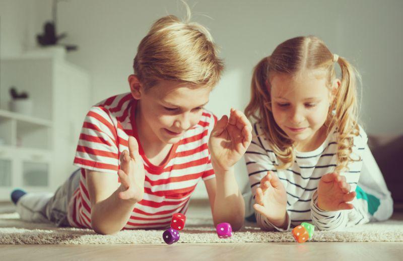 Portrat-von-zwei-frohlichen-Kindern-die-auf-dem-Boden-liegen-und-Brettspiel-spielen