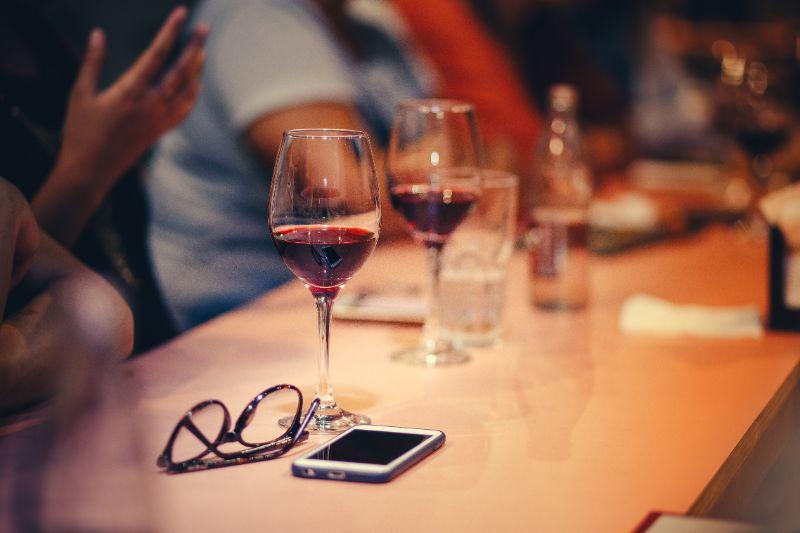 Rotwein-Glaser-und-Handy-auf-Stehtisch