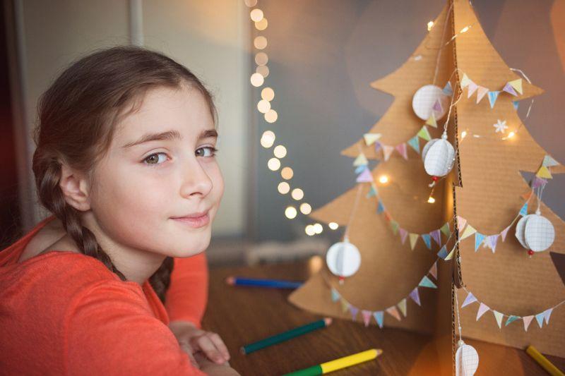 Weihnachtsbaum-aus-Pappe-verziert-mit-Kugeln-und-Girlanden-aus-Flaggen.-Kind-macht-Kunsthandwerk-fur-das-neue-Jahr-in-der-Schule