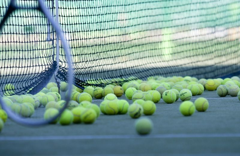 ein-Tennis-Recket-und-viele-Tennisballe