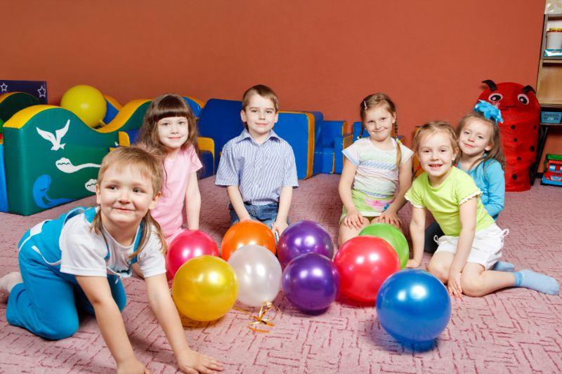 kinder-mit-vielen-Ballons-auf-dem-Boden