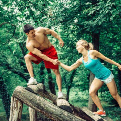 Fitness Trail Paar überquert Hindernis