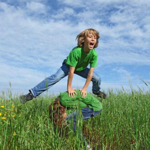 Gluckliche-gesunde-Kinder-die-im-Sommer-im-Freien-Bockspringen-spielen