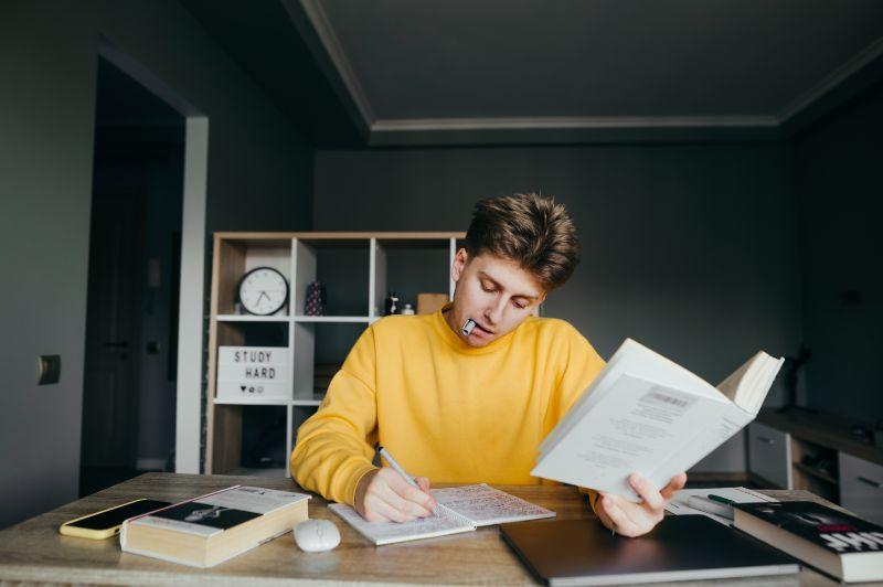 Hubscher-junger-mannlicher-Student-in-gelber-Freizeitkleidung-studiert-zu-Hause-an-einem-Tisch-halt-Buch-in-der-Hand-und-schreibt-aufmerksam-in-ein-Notizbuch-mit-einem-Stift-in-den-Zahnen.