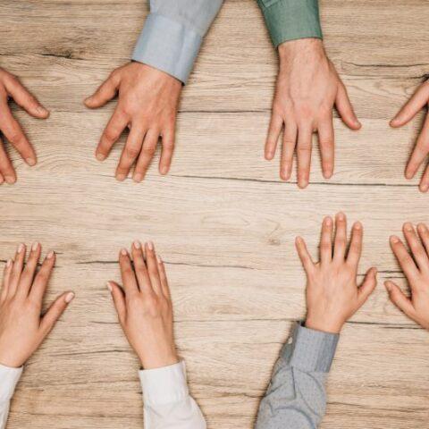 Draufsicht der Leute mit Händen auf Holztisch