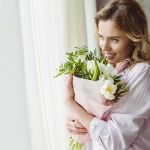 Frauentag, eine schöne Frau, die einen schönen Blumenstrauß hält