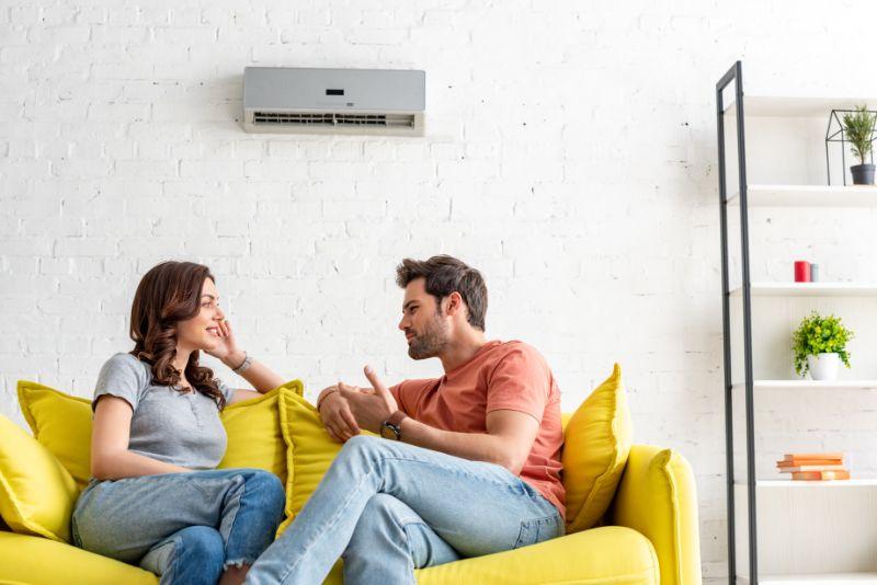 Frohlicher-Mann-und-Frau-sprechen-wahrend-sie-auf-gelbem-Sofa-unter-Klimaanlage-zu-Hause-sitzen