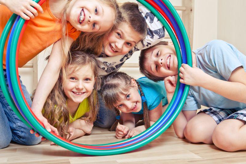 Funf-frohliche-Kinder-die-durch-Hula-Hoops-schauen