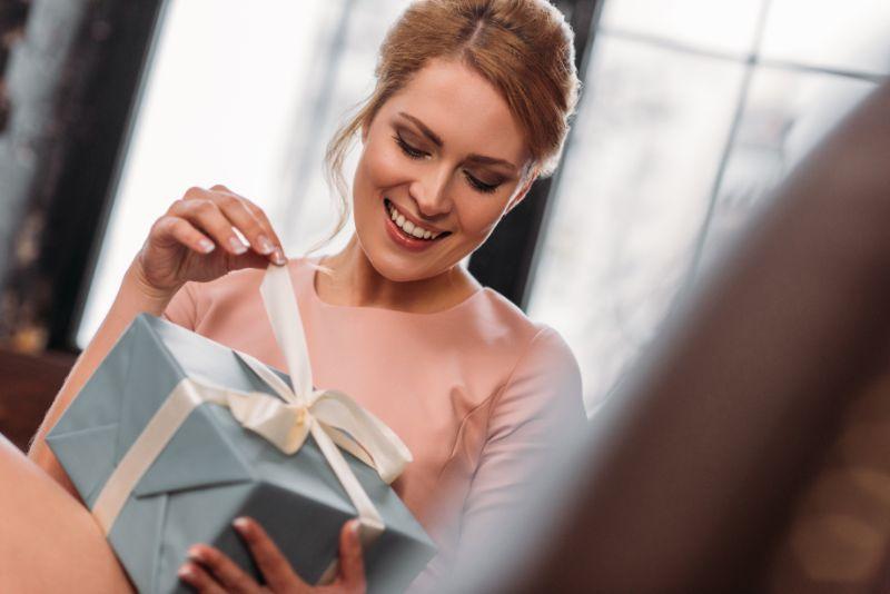 Gluckliche-junge-Frau-die-Frauentagsgeschenk-offnet