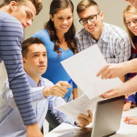 Gruppe von Schülern und Lehrern mit Laptop