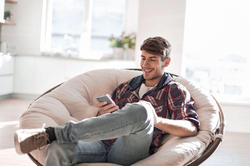 Junger-Mann-der-Nachrichten-auf-seinem-Smartphone-liest