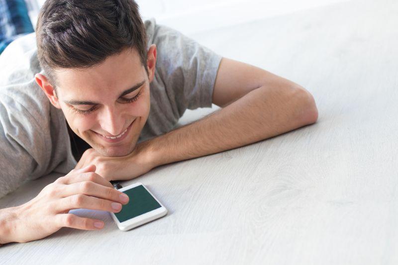 Junger-Mann-mit-Handy-zu-Hause