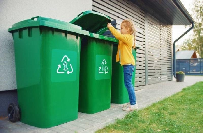 Junges-Madchen-wirft-eine-leere-Plastikflasche-in-einen-Mulleimer.-Sie-verwendet-den-richtigen-Mulleimer-weil-diese-Familie-Abfalle-sortiert-und-dabei-hilft-die-Umwelt-zu-schonen.