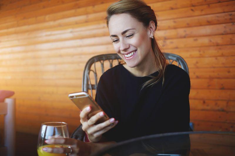 Madchen-das-an-ihrem-Handy-lachelt