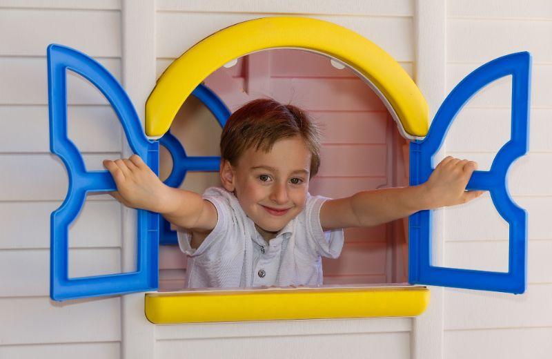 Nettes-Kind-das-im-Spielzeughaus-spielt