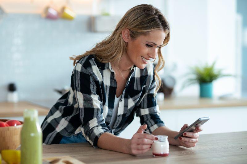 Schuss-der-schonen-reifen-Frau-die-Joghurt-isst-wahrend-Nachrichten-mit-Smartphone-in-der-Kuche-zu-Hause-senden.