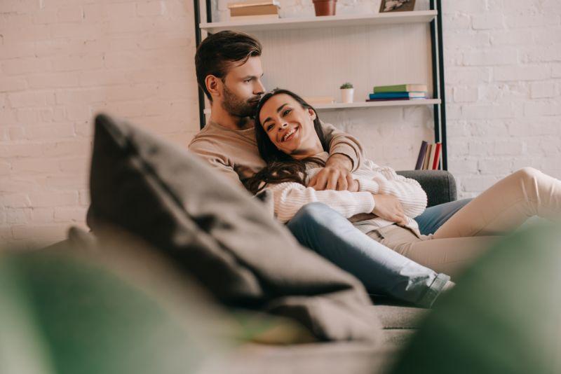 Attraktives-junges-Paar-das-zu-Hause-auf-der-Couch-kuschelt