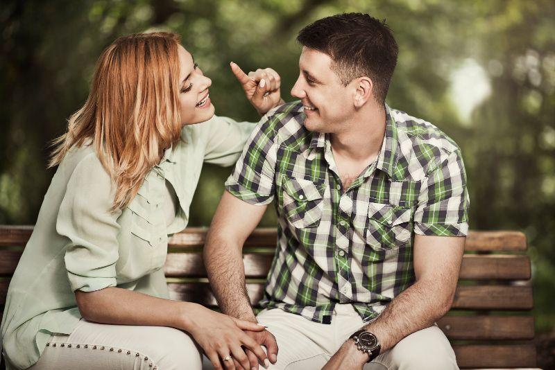 Fröhliches Paar, das draußen spricht und lächelt.
