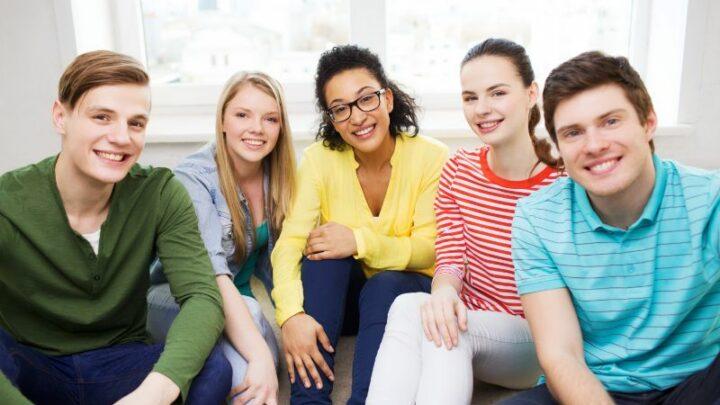 Fünf lächelnde Teenager, die Spaß zu Hause haben