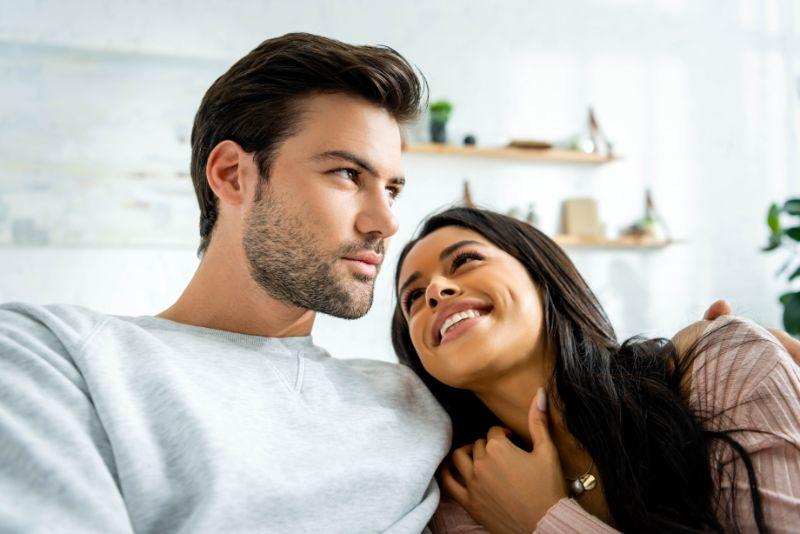 Gluckliche-junge-Frau-die-ihren-Freund-auf-der-Couch-zu-Hause-umarmt