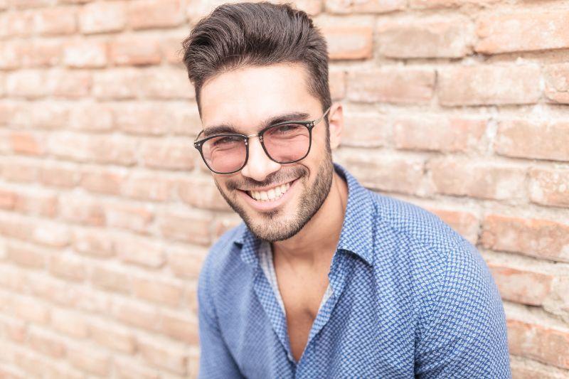 Glucklicher-lachelnder-Mann-mit-Glasern-der-gegen-eine-Mauer-lehnt