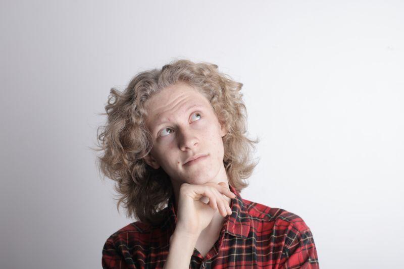 Mann-mit-blonden-lockigen-Haaren-denkt