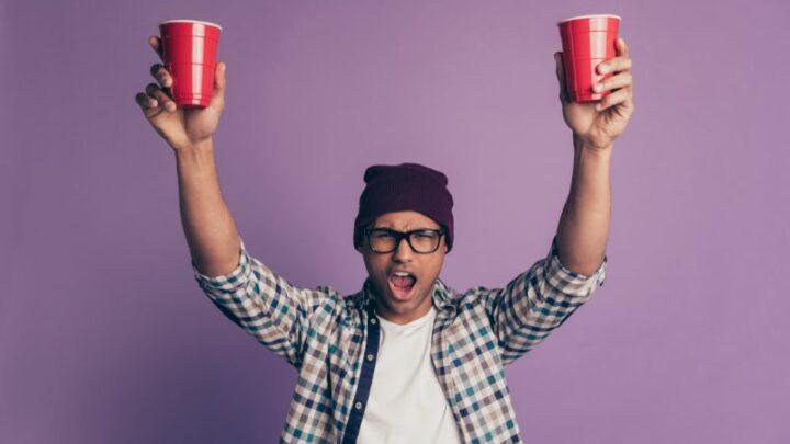 fröhlich froh, verrückt betrunken sorglos in Brillen Kerl hält in Händen Plastikbecher