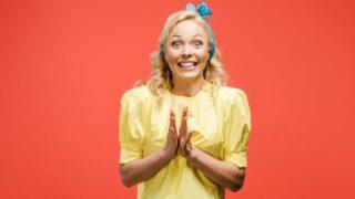 Blonde Frau in Gelb die sich freut