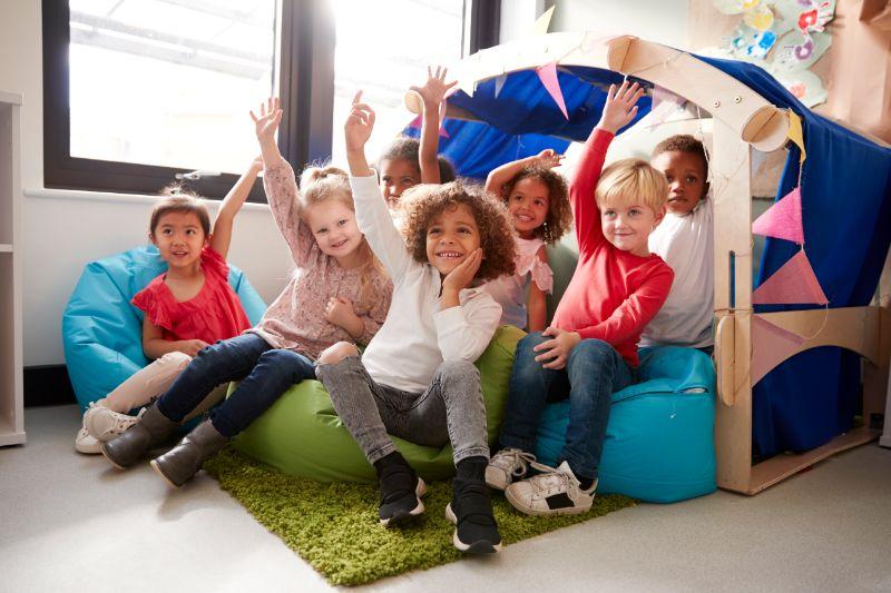 Eine-multiethnische-Gruppe-von-Schulkindern-sitzt-auf-Sitzsacken-in-einer-bequemen-Ecke-des-Klassenzimmers-und-hebt-die-Hande-um-eine-Frage-zu-beantworten