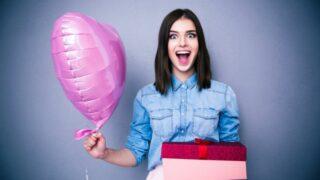 Erstaunte Frau, die Ballon und Geschenkbox hält