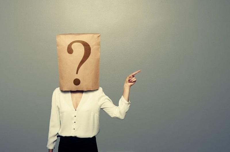 Frau-mit-Papiertute-mit-Fragezeichen-auf-etwas-zeigend