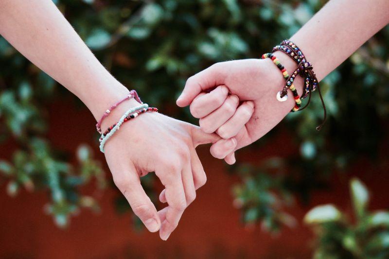 Freunde-die-Hande-halten-und-Freundschaftsbander-tragen