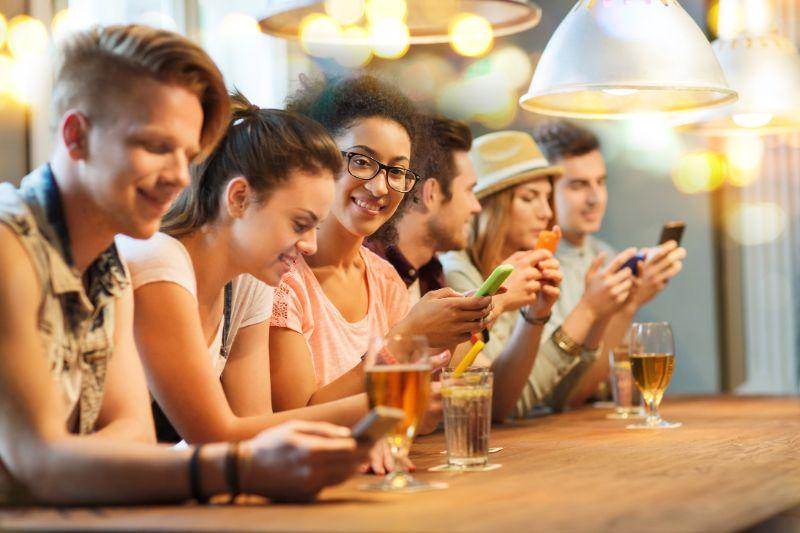 Freunde-mit-Smartphones-und-Getranken-an-der-Bar