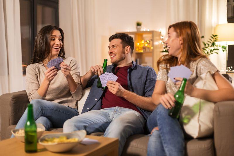 Freunde-spielen-Karten-und-trinken-Bier-zu-Hause