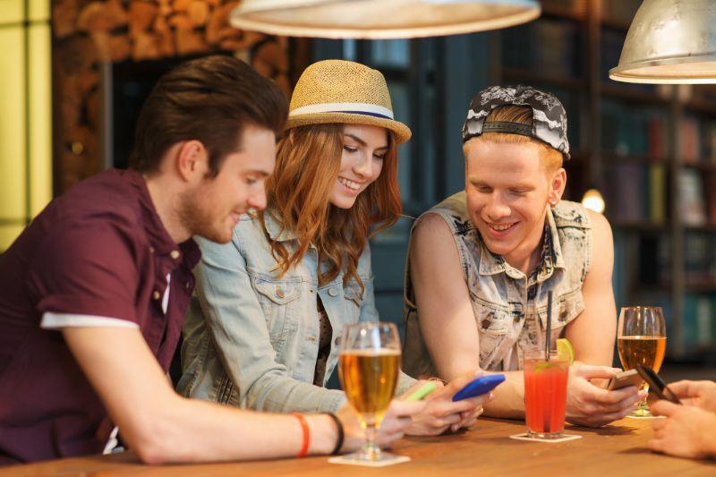 Gluckliche-Freunde-mit-Handys-und-Getranken-an-der-Bar