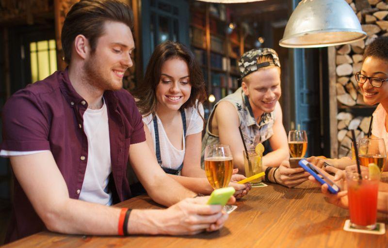 Gluckliche-Freunde-mit-Smartphones-und-Getranken-an-der-Bar