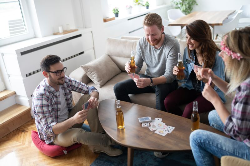 Gluckliche-Gruppe-von-Freunden-die-Karten-spielen-und-trinken-2