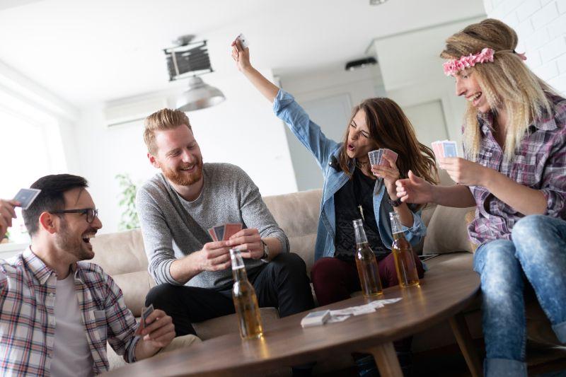 Glückliche Gruppe von Freunden, die Karten spielen und trinken