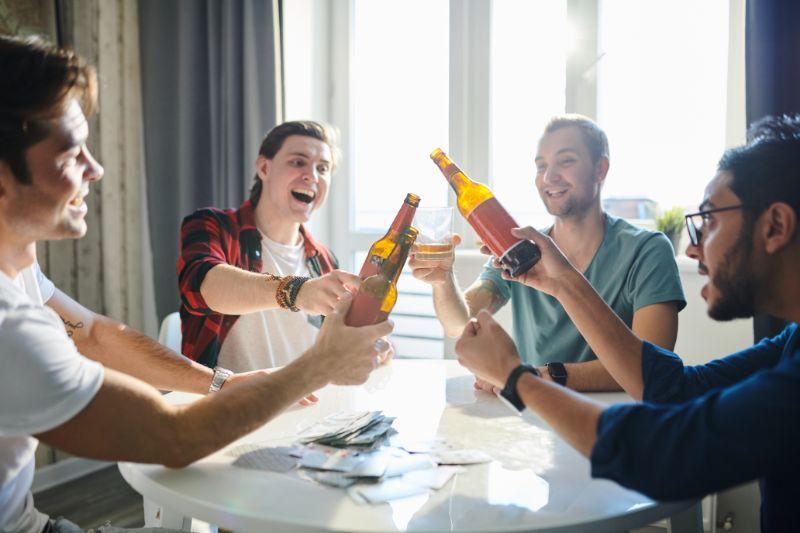 Gluckliche-junge-Manner-die-am-Tisch-sitzen-und-rosten