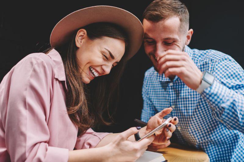 Gluckliches-Paar-in-der-Liebe-lachend-wahrend-Sie-lustiges-Video-ansehen