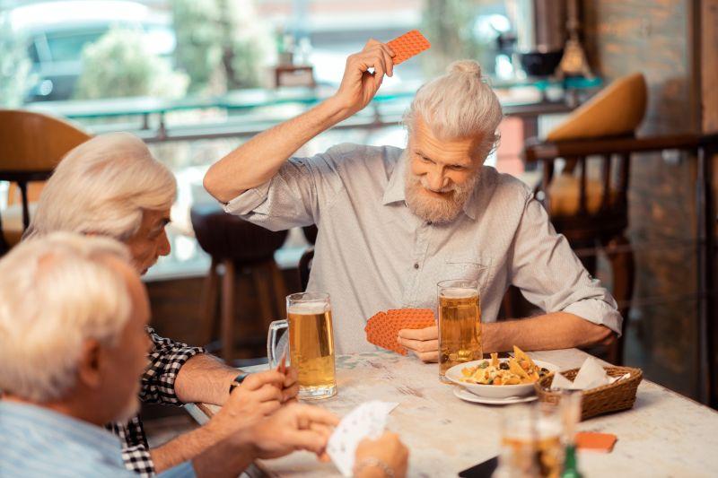 Grauhaarige-Rentner-spielen-Karten-und-trinken
