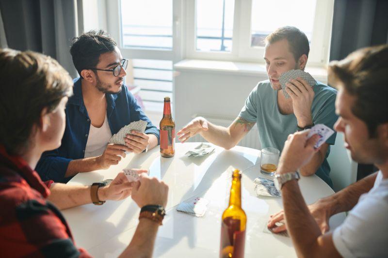 Gruppe-mannlicher-Freunde-die-Karten-am-Tisch-spielen-und-trinken