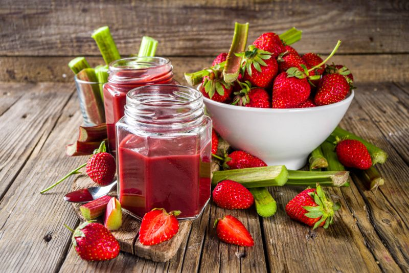 Hausgemachte-Erdbeer-Rhabarber-Marmelade-oder-Sauce-mit-frischem-Rhabarber-und-Erdbeeren-und-Gewurzen-rustikalem-Holzhintergrund