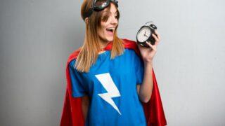 Hübsches Superheldenmädchen, das Weinleseuhr auf einem grauen strukturierten Hintergrund hält