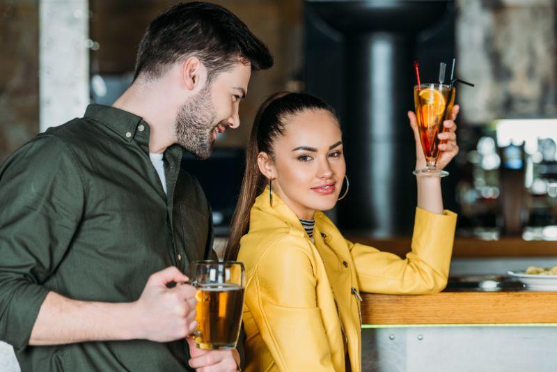 Junge Frau mit Cocktail, Mann, der versucht, mit ihr zu sprechen