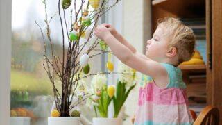 Kleines Mädchen, das nach Hause für Ostern verziert