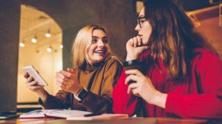 Lächelnde beste Freundinnen, die während der Freizeit während der Kaffeepause während des Studiums ein Gespräch führen.