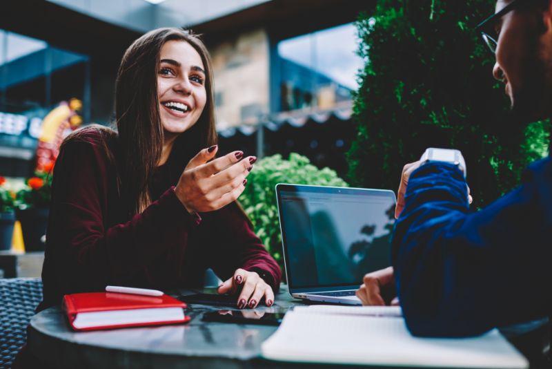 Lachelndes-weibliches-Hipster-Madchen-das-lustige-Geschichte-erzahlt-die-mit-mannlichem-Kollegen-kommuniziert-der-zusammen-am-Studentenprojekt-arbeitet